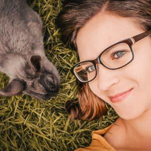 Portrait der Fotografin mit einem grauen Kaninchen in der Wiese - Hundefotografin