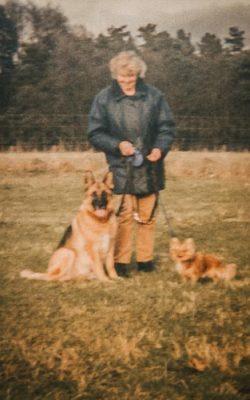 Portrait einer Frau mit Schäferhund und Chihuahua auf einer Wiese - Hundefotografin