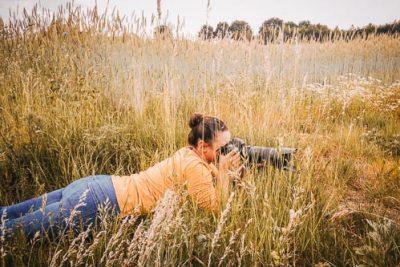 Portrait einer Fotografin bei der Arbeit in einer Wiese - Hundefotografin